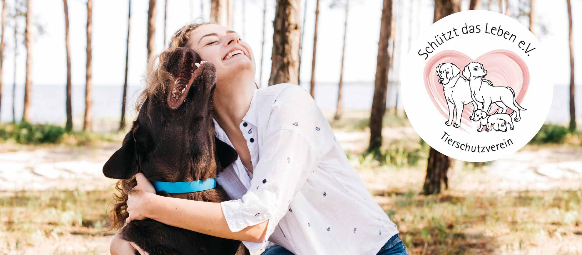 Frau umarmt ihren Hund freudig lächelnd im Wald vor Wasserkulisse